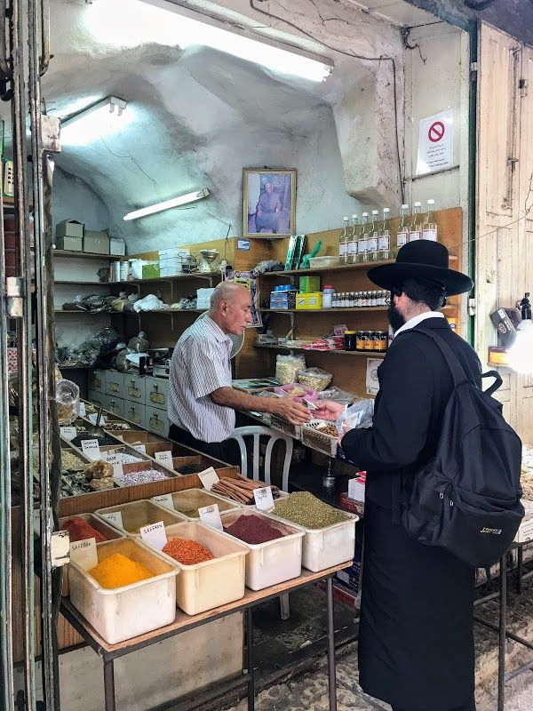 An orthodox Jewish customer buys from an Arab shopkeeper